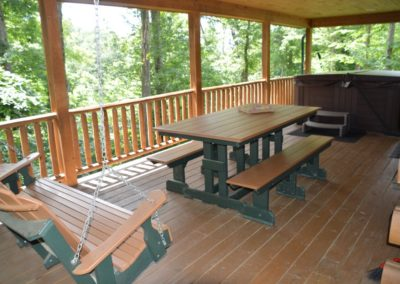 deck with porch swing and picnic table at Escape log cabin