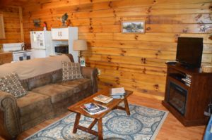 TV area with sofa in The Landing log cabin