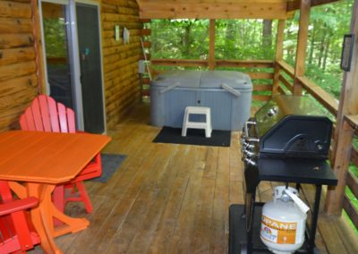 deck with gas grill and hot tub at The Overlook log cabin