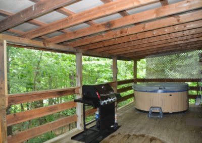 back porch with hot tub on porch of The Lakota log cabin
