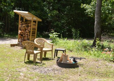fire pit with chairs and stacked firewood