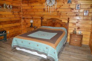 rustic bedroom with queen bed at Trail Ridge cabin